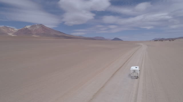aerial of pick up camper is driving over a dirt road in the andean mountains - salt flat stock videos & royalty-free footage