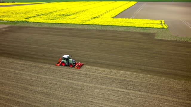 vídeos de stock e filmes b-roll de aerial of plowed field with tractor - trator