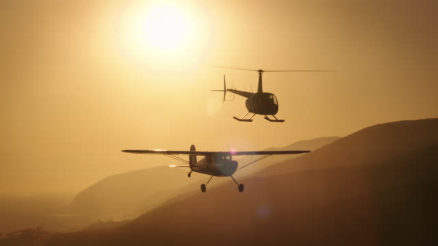 Aerial of polished metal Cessna 140 aircraft and Robinson R44 Helicopter flying in formation, in warm backlight, with the Pacific Ocean and coastal mountains in the BG, California, in late afternoon.