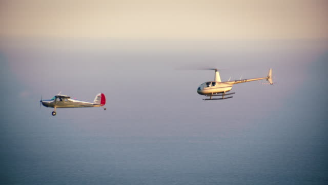 Aerial of polished metal Cessna 140 aircraft and Robinson R44 Helicopter flying in formation, in profile, with the Pacific Ocean in the BG, California, in late afternoon.