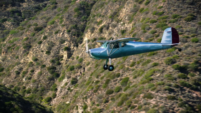 Aerial of polished metal Cessna 140 aircraft flying along the Santa Monica Mountains, zoom into cockpit, near Malibu, CA, in daytime.