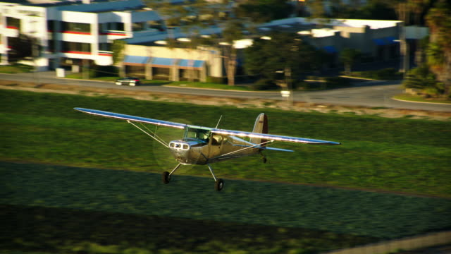 aerial of polished metal cessna 140 aircraft flying at low altitude, with farm fields in the bg, california, in daytime. - camarillo stock videos & royalty-free footage