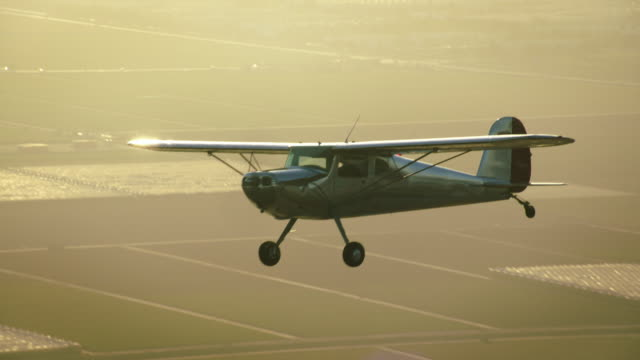Aerial of polished metal Cessna 140 aircraft flying in warm backlight, with farm fields in the BG, California, in late afternoon.