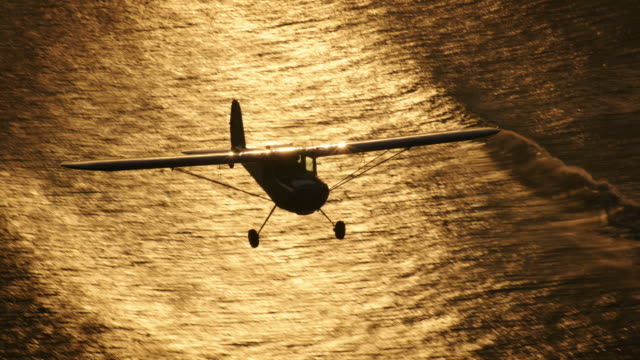 Aerial of polished metal Cessna 140 aircraft, in warm backlight, with the Pacific Ocean glittering in the BG, California, in late afternoon.