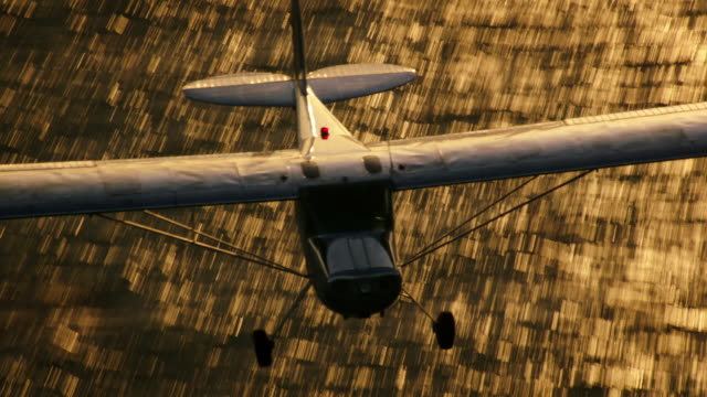Aerial of polished metal Cessna 140 aircraft, in warm backlight, with the Pacific Ocean glittering in the BG, Zoom out to wide shot, California, in late afternoon.