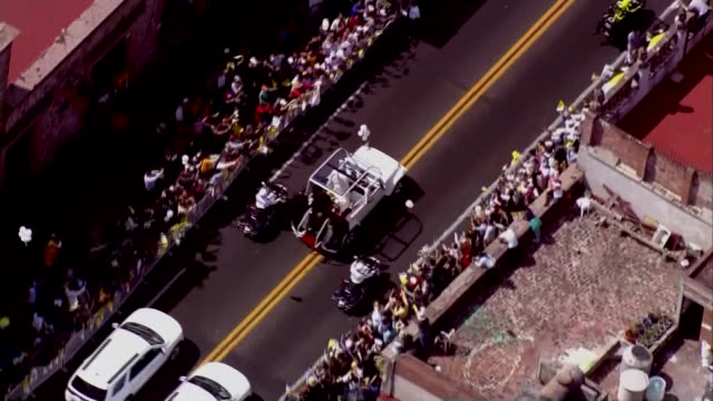 aerial of pope francis motorcade as he drives through street in morelia, mexico. bystanders cheer and wave flags from the street - morelia video stock e b–roll