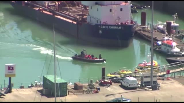 aerial of port in dover, with border force boat and dinghy of migrant asylum seekers arriving - small boat stock videos & royalty-free footage