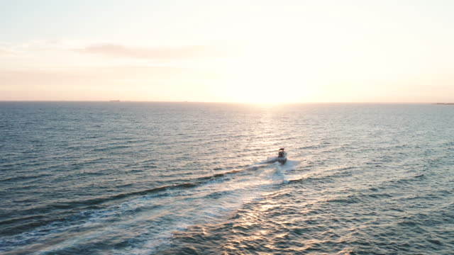 aerial of recreational boat going out to sea at sunset. - fischerboot stock-videos und b-roll-filmmaterial