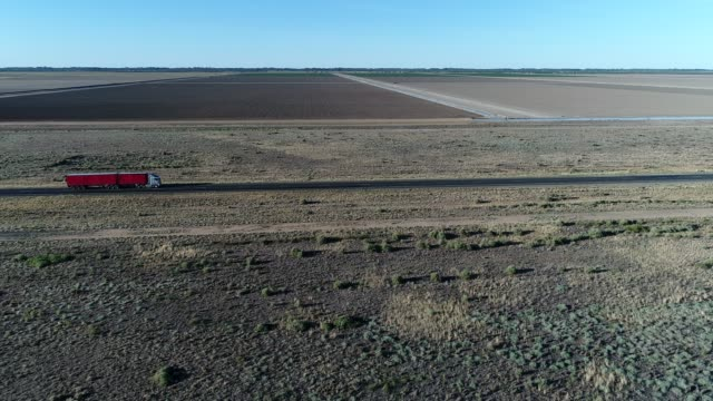 aerial of red truck driving through outback desert landscape - hay truck stock videos & royalty-free footage