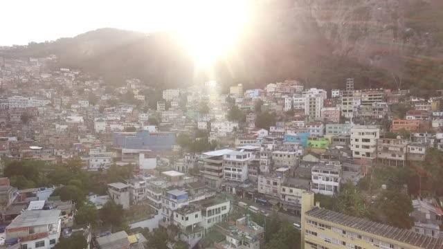 vídeos de stock e filmes b-roll de aerial of rio de janeiro nieghborhood with sun over the mountain - rio de janeiro