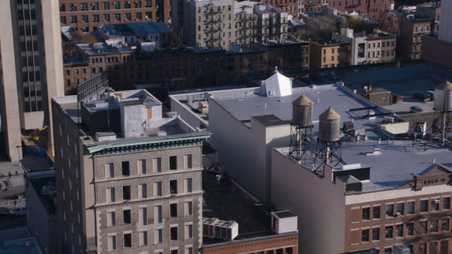 aerial of rooftops of multi-story office or apartment buildings. new york. harlem. water tanks.
