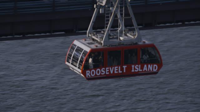 vídeos de stock, filmes e b-roll de aerial of roosevelt island tram over east river. - teleférico veículo terrestre comercial