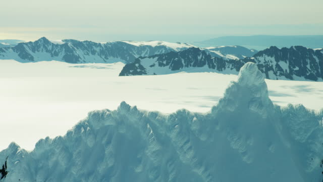 aerial of rugged glacial mountains and snow alaska - eco tourism video stock e b–roll