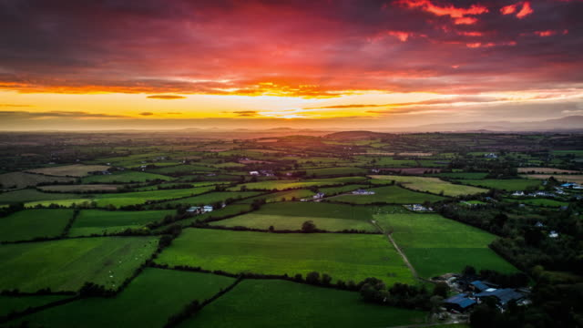 Aerial of rural landscape with fields and farmland under dramatic sunset sky, Ireland