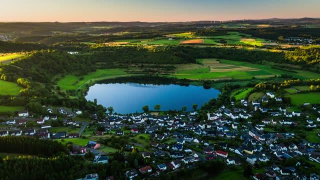 Aerial of rural landscape with village next to a lake - Schalkenmehrener Maar in Germany