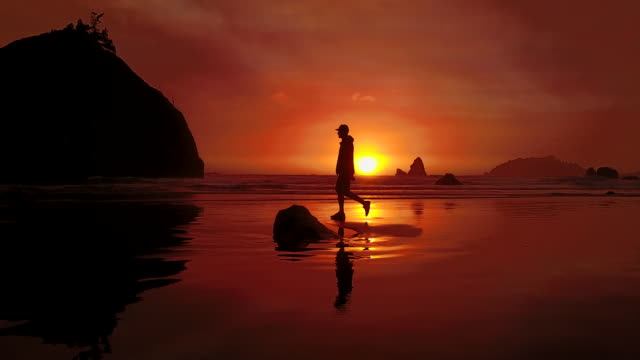 aerial of silhouette of man on houda beach - hood clothing stock videos & royalty-free footage