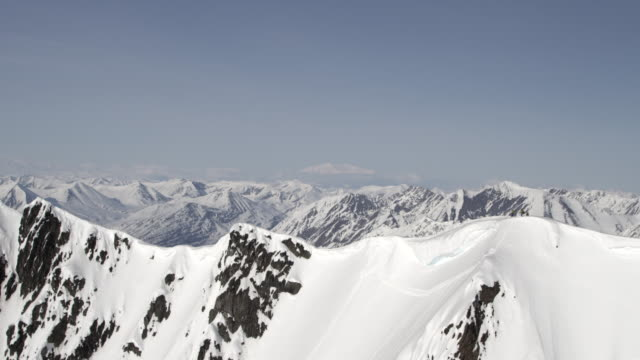 Aerial of skiers standing on summit of Alaskan peak