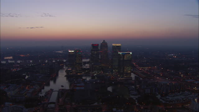 vídeos de stock e filmes b-roll de aerial of skyscrapers alongside former docks in canary wharf at dusk / london - hsbc towers