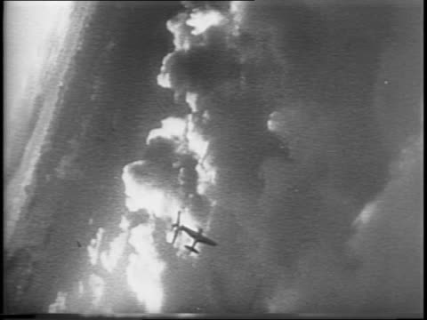 Aerial of smoke billowing from an island / montage of dogfights in the sky tracers visible shots from plane swooping down from the sky and firing on...