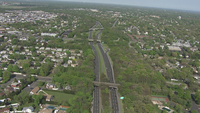 Aerial of Southern State Parkway in north Massapequa - north Amityville area of Long Island. cars driving. suburban homes, house rooftops, trees, grass, overpasses, traffic, cars, fields visible. sunny, blue skies.