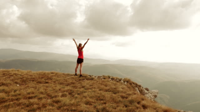 Aerial of sportswoman standing on mountain ridge with raised hands
