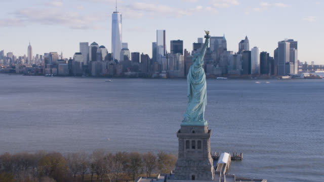 vídeos de stock, filmes e b-roll de aerial of statue of liberty in new york harbor. landmarks. downtown manhattan city skyline and new world trade center in bg. - torre da liberdade nova iorque