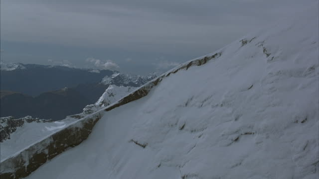 aerial of steep snow covered mountain sides. - hoch position stock-videos und b-roll-filmmaterial