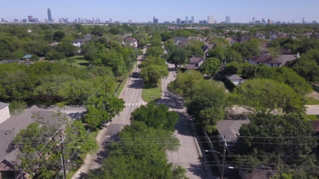 aerial of suburban street, city skyline in background - overhead view stock videos & royalty-free footage