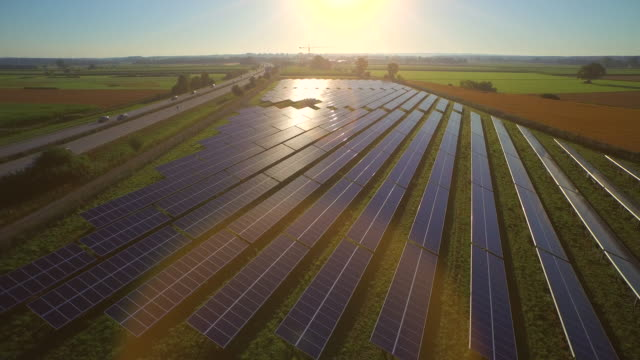 aerial of sun reflecting on panels of solar power station, lr pan - solar panels stock videos & royalty-free footage