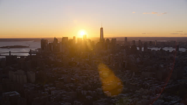 aerial of sunset and downtown manhattan new york city skyline.. skyscrapers and high rise office or apartment buildings. sun halations. - world trade centre manhattan stock videos and b-roll footage