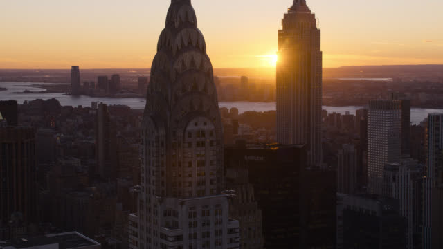 aerial of sunset and midtown manhattan new york city skyline.. skyscrapers and high rise office or apartment buildings. empire state building and chrysler building. sun halations. - world trade centre manhattan stock videos and b-roll footage