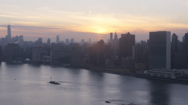 aerial of sunset over midtown manhattan new york city skyline. skyscrapers and high rise office or apartment buildings. east river in fg.