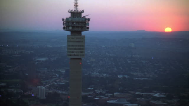 vídeos de stock e filmes b-roll de aerial of the hillbrow tower moving further away to reveal johannesburg central business district at sunset/sunrise - joanesburgo