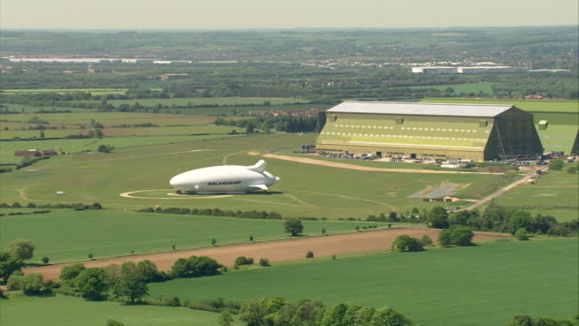 aerial of the hybrid air vehicle, the airlander 10, at cardington airfield - airplane hangar stock videos & royalty-free footage
