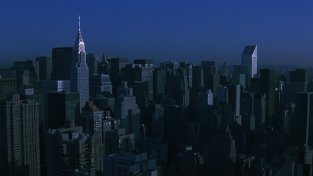 stockvideo's en b-roll-footage met aerial of the new york city skyline, including the chrysler and u.n. buildings, during golden hour. - stroomuitval