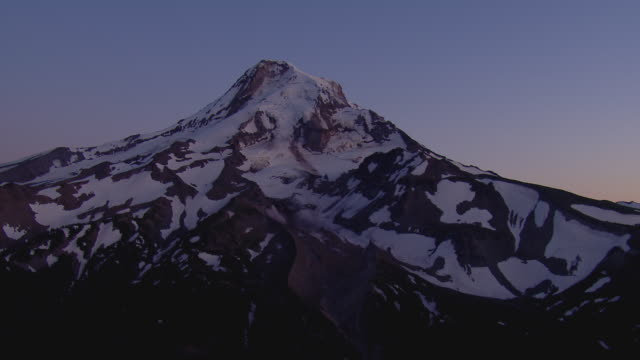 Aerial of the snow covered peak of Mt. Hood in the moonlight.