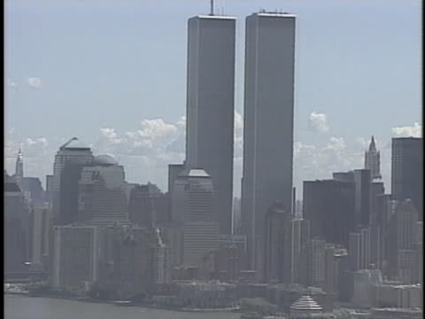 aerial of the statue of liberty and world trade center's twin towers. - world trade center manhattan stock-videos und b-roll-filmmaterial