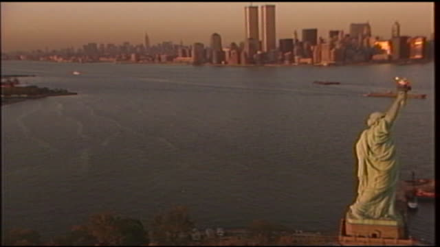 aerial of the statue of liberty as it wraps around the statue a reveal is made of the new york city skyline at sunset - aerial or drone pov or scenics or nature or cityscape stock-videos und b-roll-filmmaterial