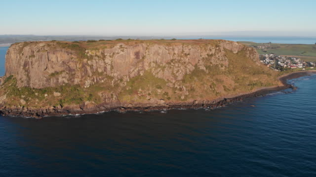 4k aerial of the 'the nut', impressive headland behind which shelters the picturesque town of stanley on the far north western coast of tasmania - gebäudefries stock-videos und b-roll-filmmaterial