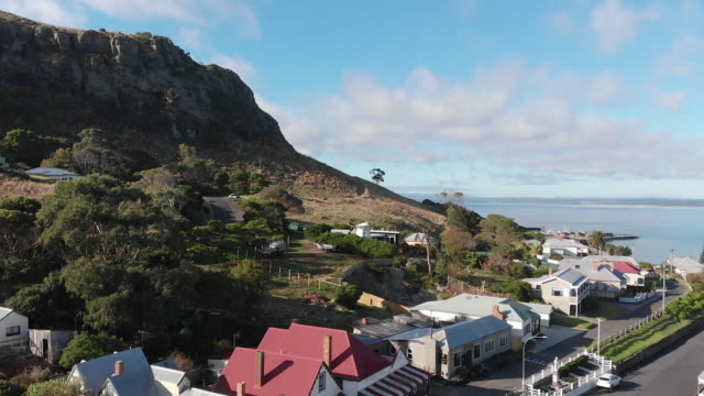 4K aerial of the 'The Nut' towering over the picturesque town of Stanley on the far north western coast of Tasmania
