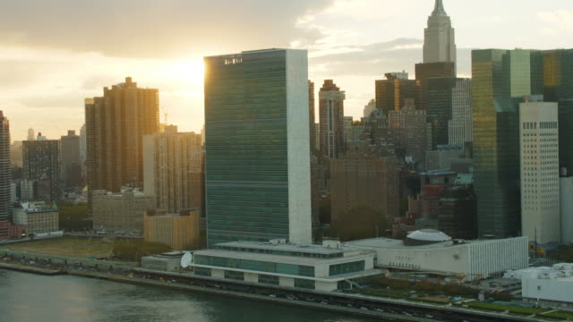 aerial of the united nations un with sun behind it, light flair - united nations stock videos & royalty-free footage