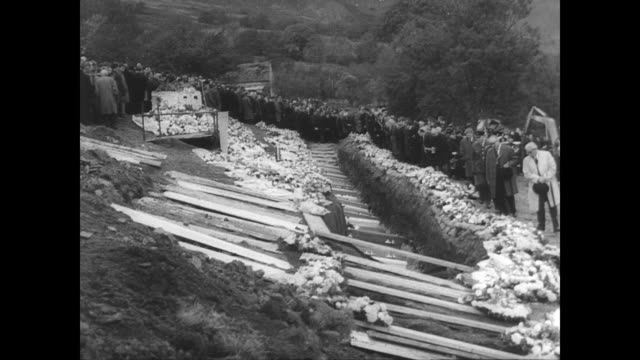 aerial of the welsh town aberfan after the rock slide that killed 116 children / above the cemetery where a cross is made out of flowers / woman... - reportage stock videos & royalty-free footage