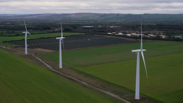 aerial of three wind turbines in front of solar panels - ethik und moral stock-videos und b-roll-filmmaterial