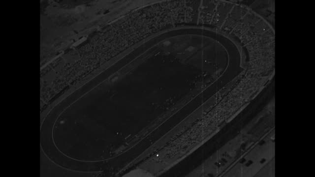 VS aerial of track field stadium / stands filled with spectators / runners in 100m at starting blocks run Jesse Owens leads from beginning to finish...