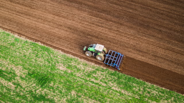 aerial of tractor plowing a field - plowed field stock videos & royalty-free footage