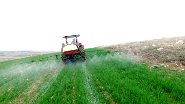 aerial of tractor spraying pesticides on an agricultural field - insecticide stock videos & royalty-free footage