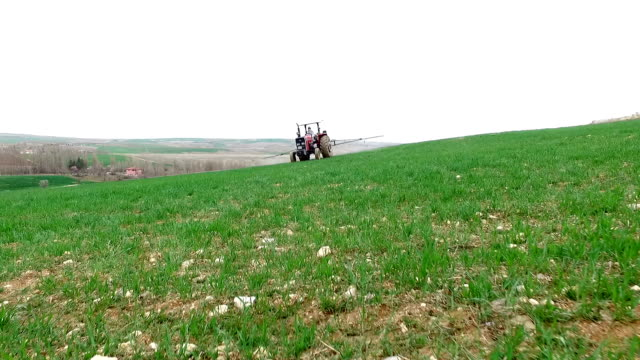 aerial of tractor spraying pesticides on an agricultural field - crop sprayer stock videos and b-roll footage
