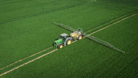 stockvideo's en b-roll-footage met luchtfoto van trekker sproeien van pesticiden op een gebied van de landbouw - tractor