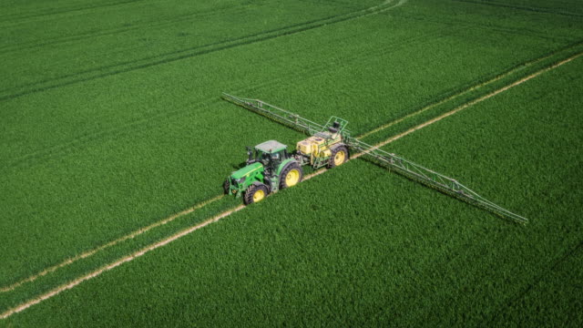 vídeos de stock e filmes b-roll de aerial of tractor spraying pesticides on an agricultural field - quinta