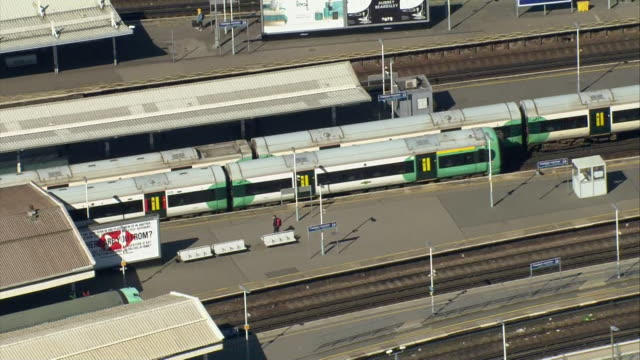 aerial of train stations with empty platforms but trains continuing to run to get key workers to jobs during coronavirus pandemic - railway station platform stock videos & royalty-free footage